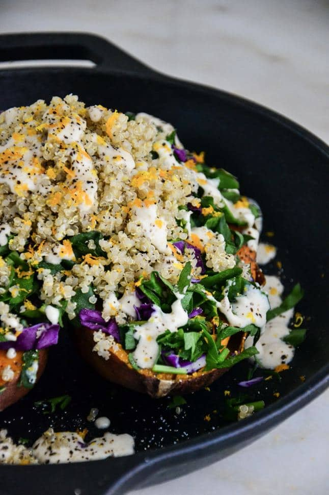 Roasted sweet potato stuffed with quinoa and greens on a skillet.