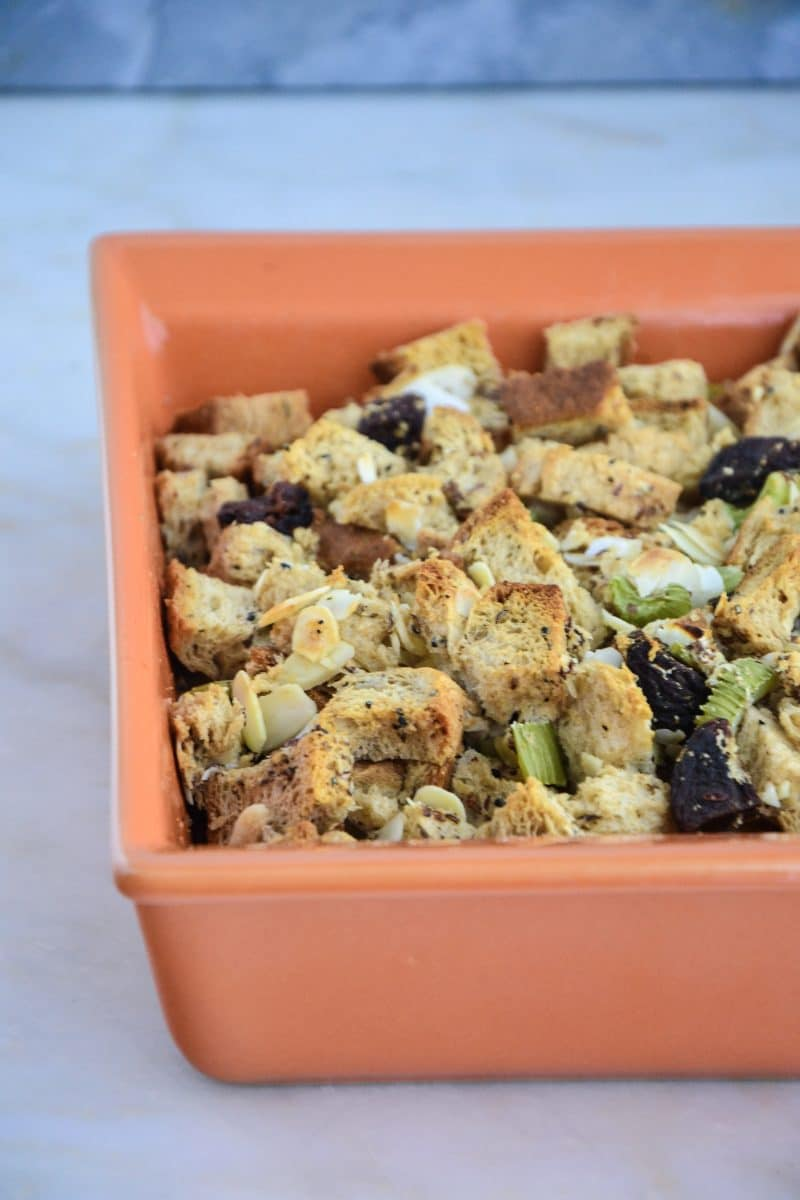 A square dish of gluten-free stuffing, including toasted bread cubes and green celery bits.