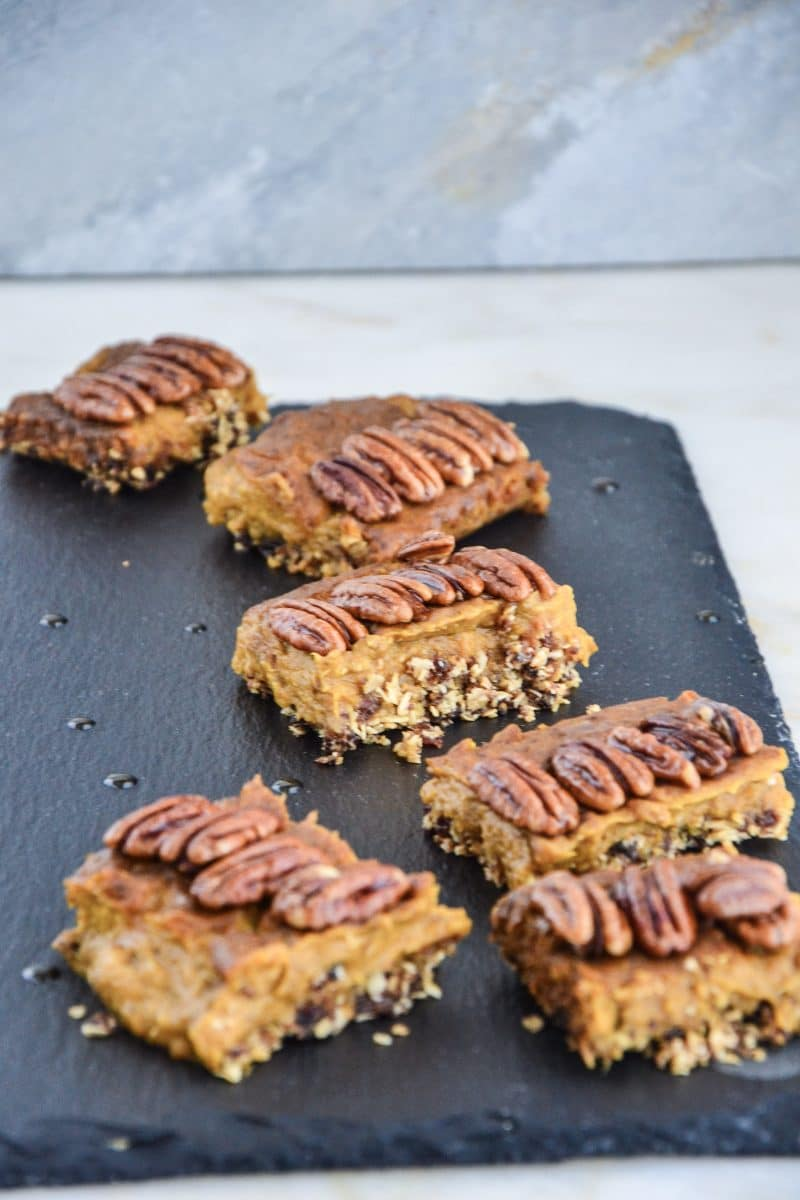 Pumpkin spice pie bars on a slate topped with four pecans each.