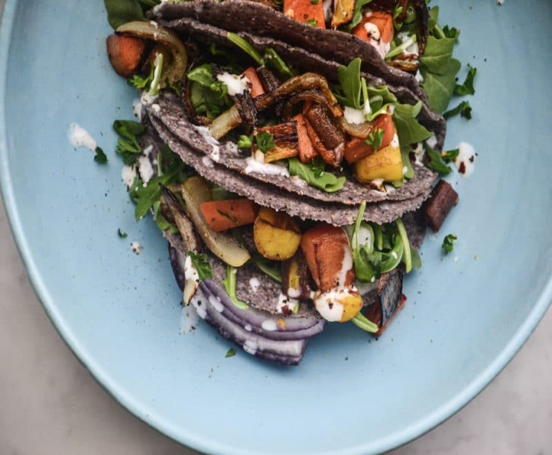 Blue corn tacos stuffed with roasted carrots, carmelized onions, and arugula.