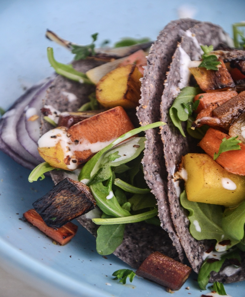 Beautiful blue corn tacos filled with yellow and orange roasted carrots and drizzled with a white sauce.