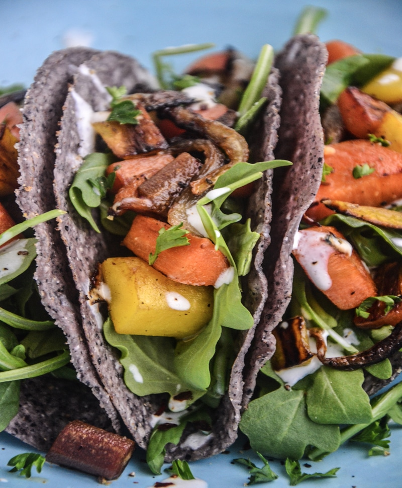 Gorgeous tacos stacked together and filled with green arugula, orange and yellow carrots, and perfectly carmelized onions.