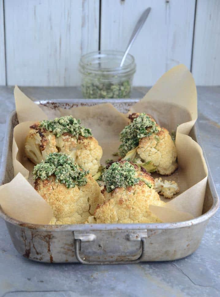 Four chunks of roasted cauliflower topped with organic gluten-free arugula pesto.