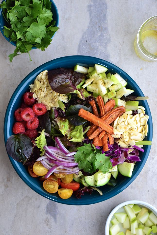 A aerial view of a delicious bowl of colorful fruits and veggies chopped into bite sized pieces.