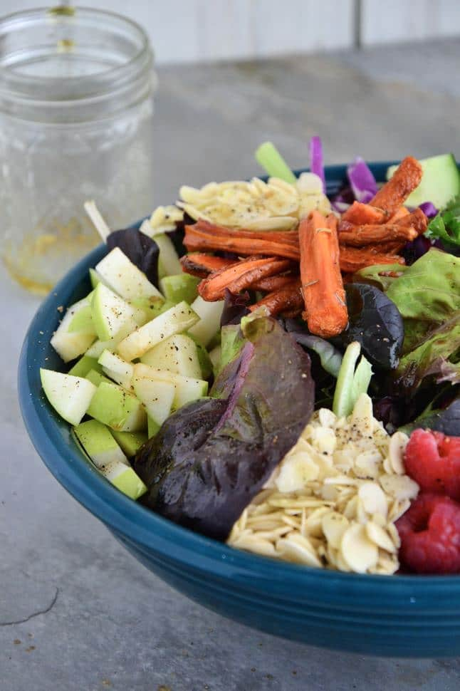 A close up of the bowl of salad with all of the ingredients piled on top.