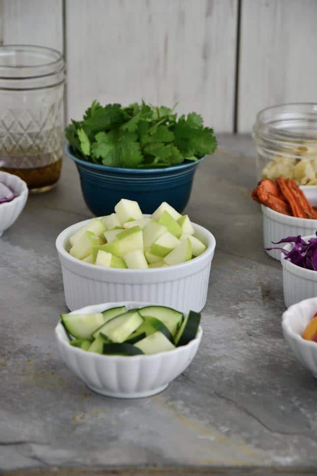 Individual cups of cut cucumber and apple surrounded by some of the other ingredients in their own bowls.