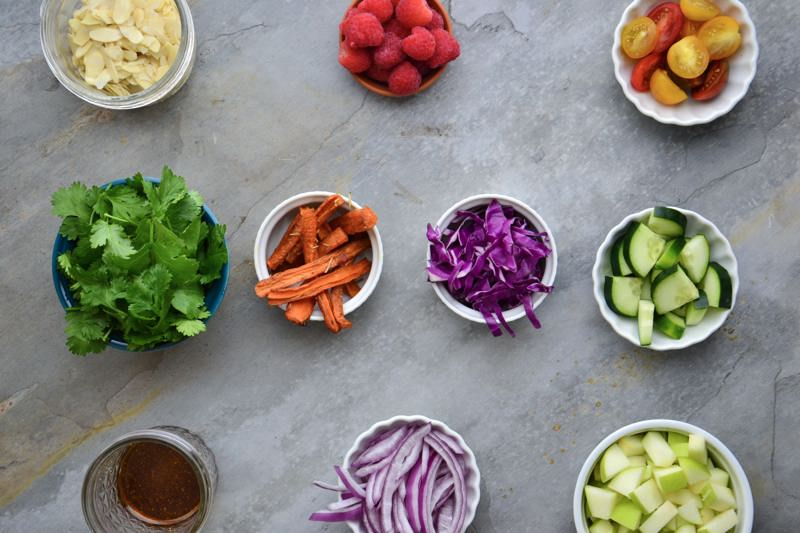 An aerial view of all of the ingredients for this salad cut and prepped in individual bowls.