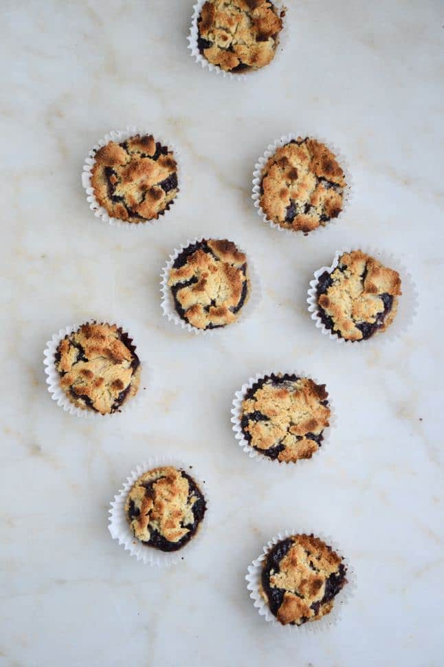 An overhead shot of a bunch of perfectly browned muffins in muffin tins on a counter.