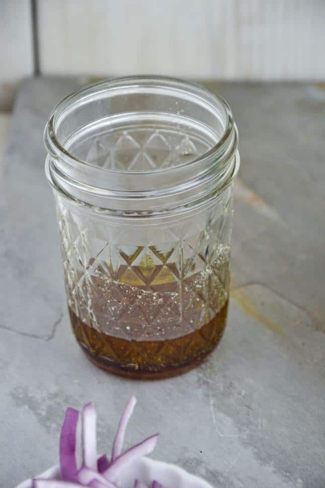 A mason jar with a serving of homemade yellowy brown salad dressing.