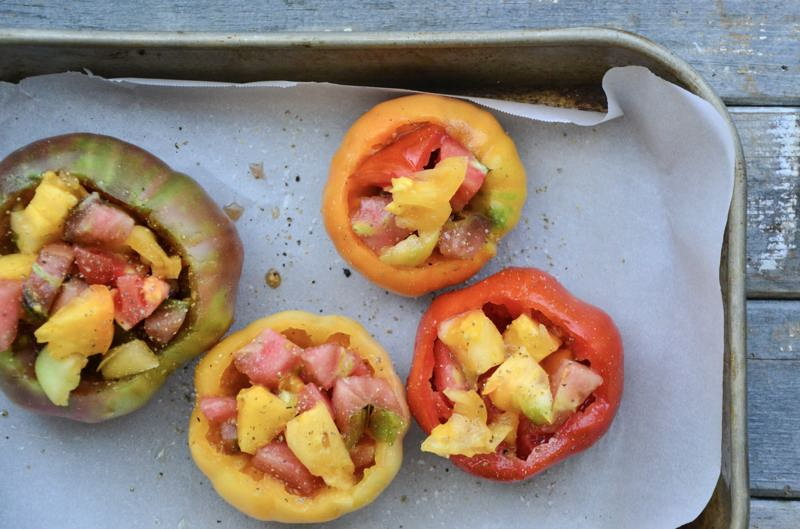Four tomatoes stuffed with quinoa and chopped tomato ready to go into the oven.