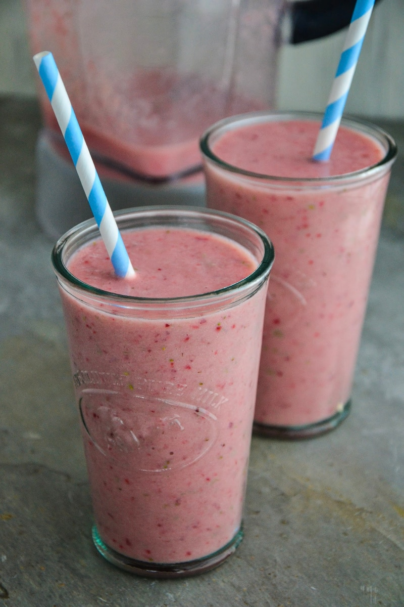 Two classes of a strawberry smoothie with a blender behind them on the counter.