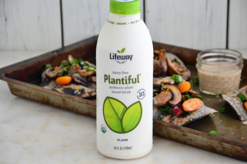 Lifeway Kefir Plantiful plain drink in front of a baking sheet with veggie fajitas.
