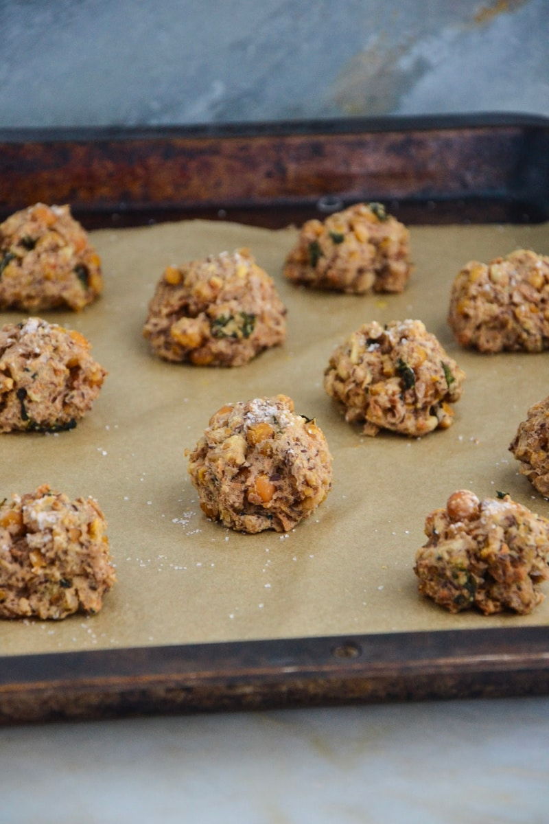 A side view of a baking sheet full of chickpea beanballs on parchment paper